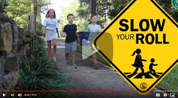 children walking along a sidewalk with the Slow Your Roll logo graphic onscreen