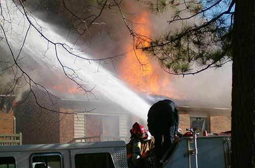 firefighter operating a fire hose to dose a home on fire
