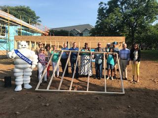 Photo of future homeowner and community partners raising a wall to celebrate a new Habitat home in p