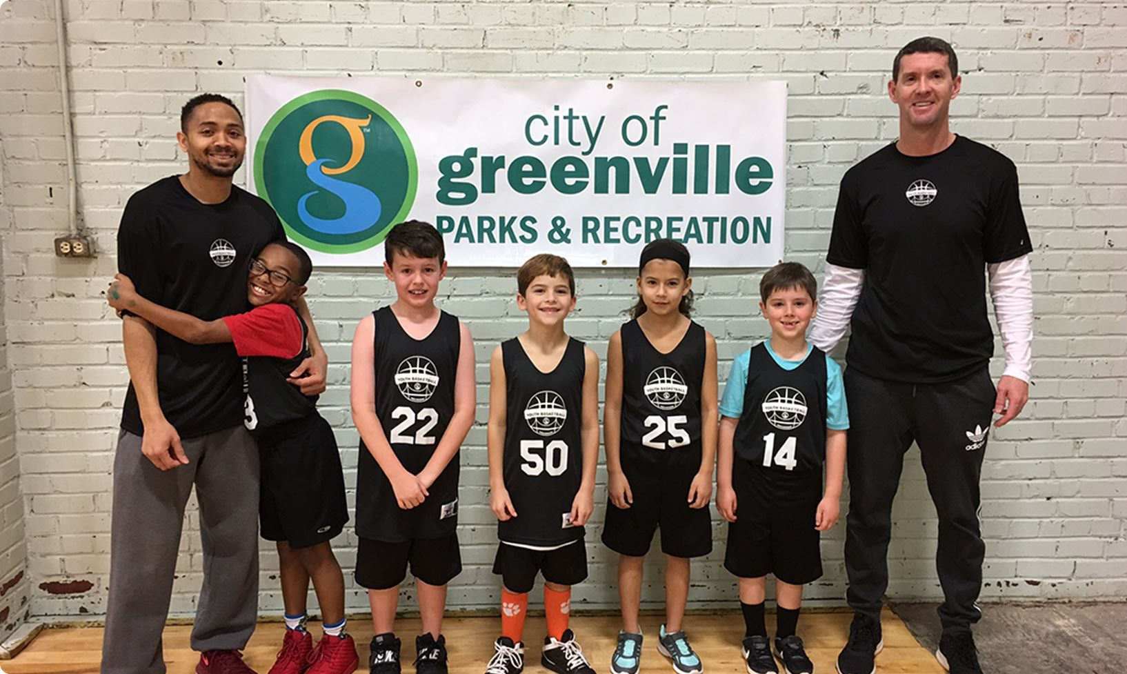 Basketball team in front of Greenville Parks and Rec sign