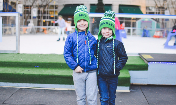 Two kids posing in front of the ice rink