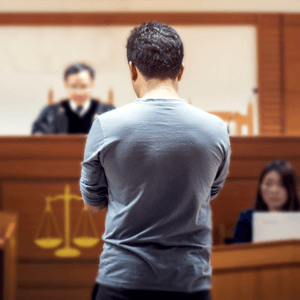 man standing in front of a judge in a courtroom