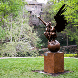 A bronze statue of a winged man atop a ball, part of the Wings of the City exhibition now on display