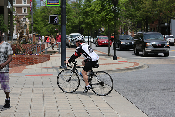 Cyclist riding Main Street in Greenville